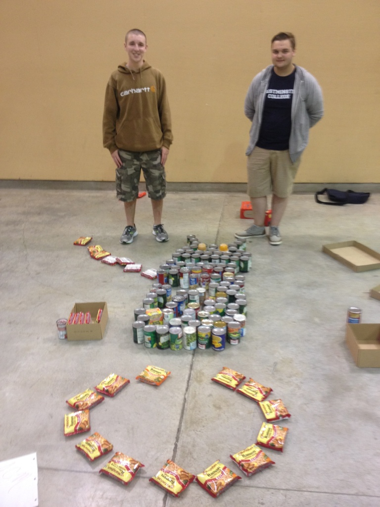 Two member of the ACM team for Westminster's 2014 Homecoming pose in front of their 'Canned Creation' of an Android symbol balancing on a circus call. The Canned Creations event collected approximately 700 cans to donate. The ACM team tied for first in the Canned Creations event. PHOTO BY ALI VEATCH