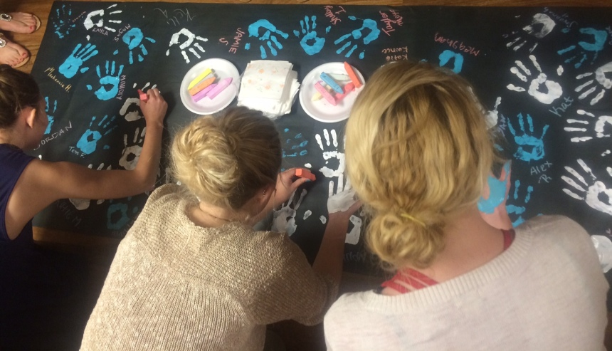 "Members of Kappa Alpha Theta add their handprints to a ""These Hands Don't Haze"" banner. PHOTO BY COURTNEY GALLAGHER."