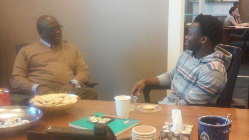 President Akande and Joseph Mbowa, '19, have a conversation over cookies. PHOTO BY STEFANIE EGGLESTON.